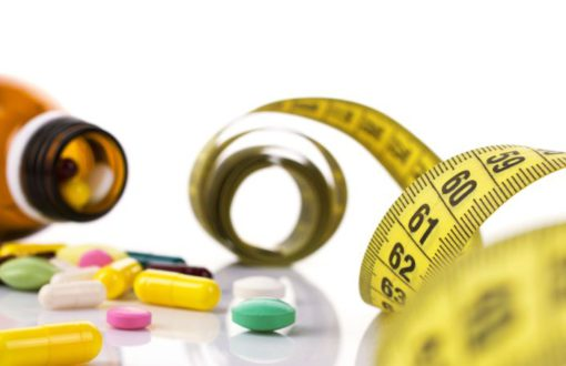 different colorful medicaments from bottle and yellow measure tape on unfocused and white background